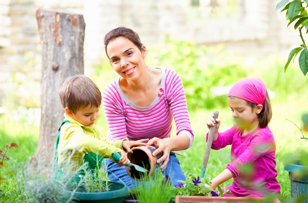 mom gardening with two kids