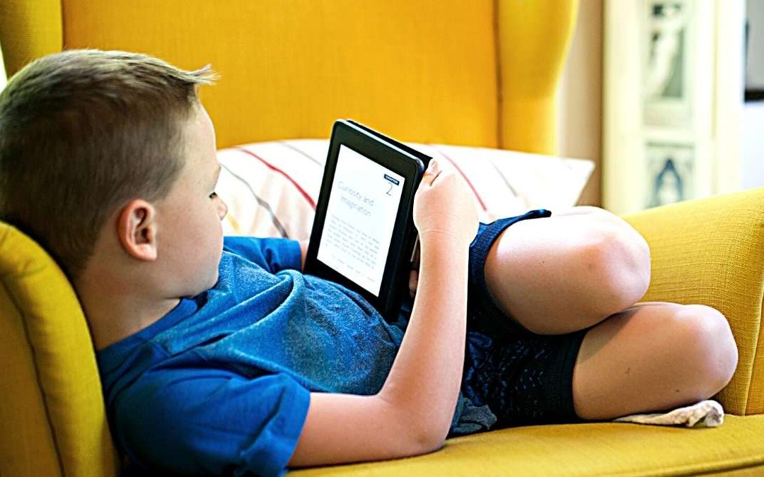 a boy lying on sofa holding tablet Screen Time For Kids During Covid lockdown