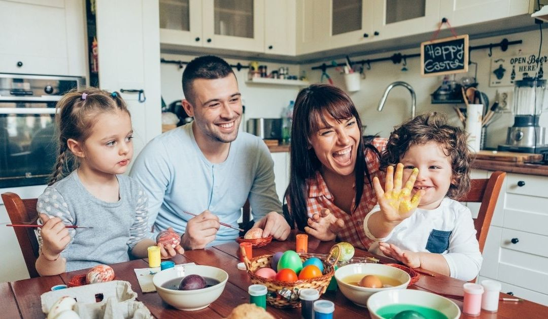 A father mother and two kids having fun Easter activity on the table