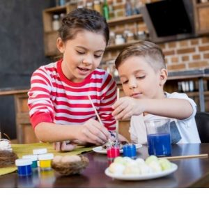 two kids having fun of painting Easter eggs