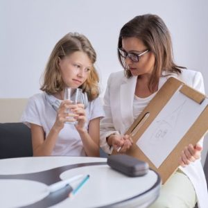 a female psychologist counsels a depressed child