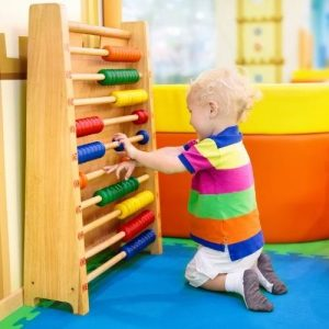 a toddler plays a colorful interactive and educational toy