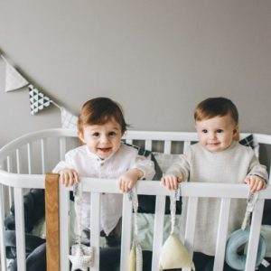 two babies standing inside a playpen play area