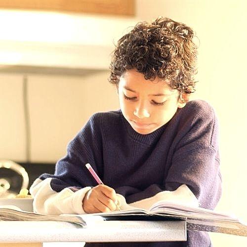 a boy writing doing his homework