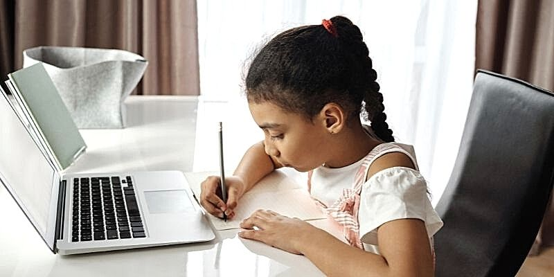 a girl writing in front of a laptop doing her homework