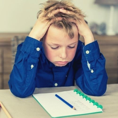 a kid holding his head stress staring at his pen and note learning homework