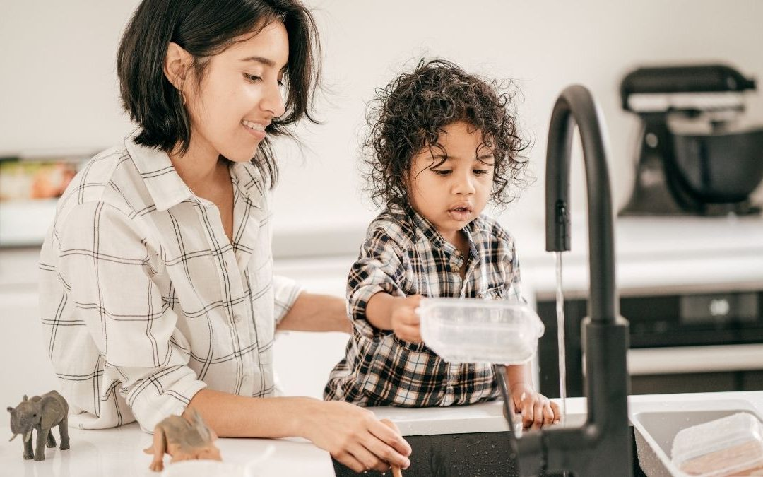 a mother bond with toddler holding a food container at the kitchen sink